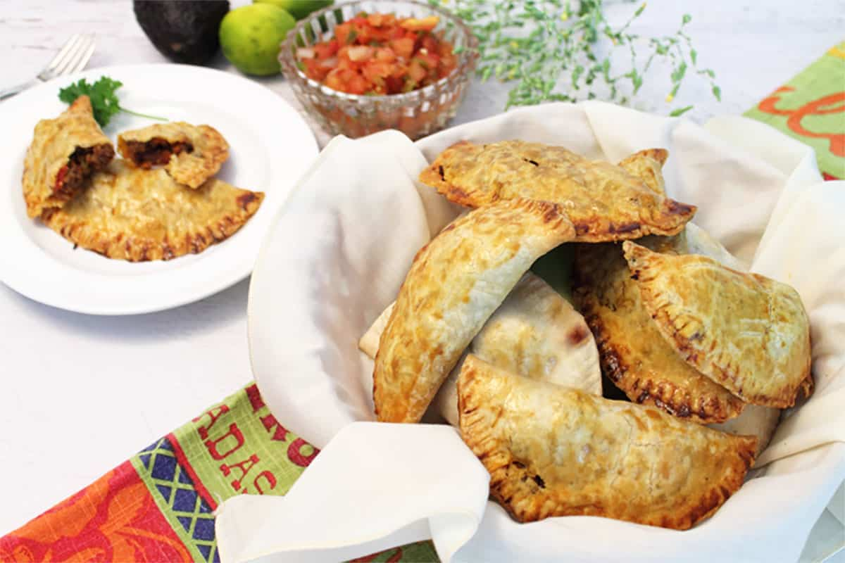 Beef empanadas in white line basket with one on plate in back.