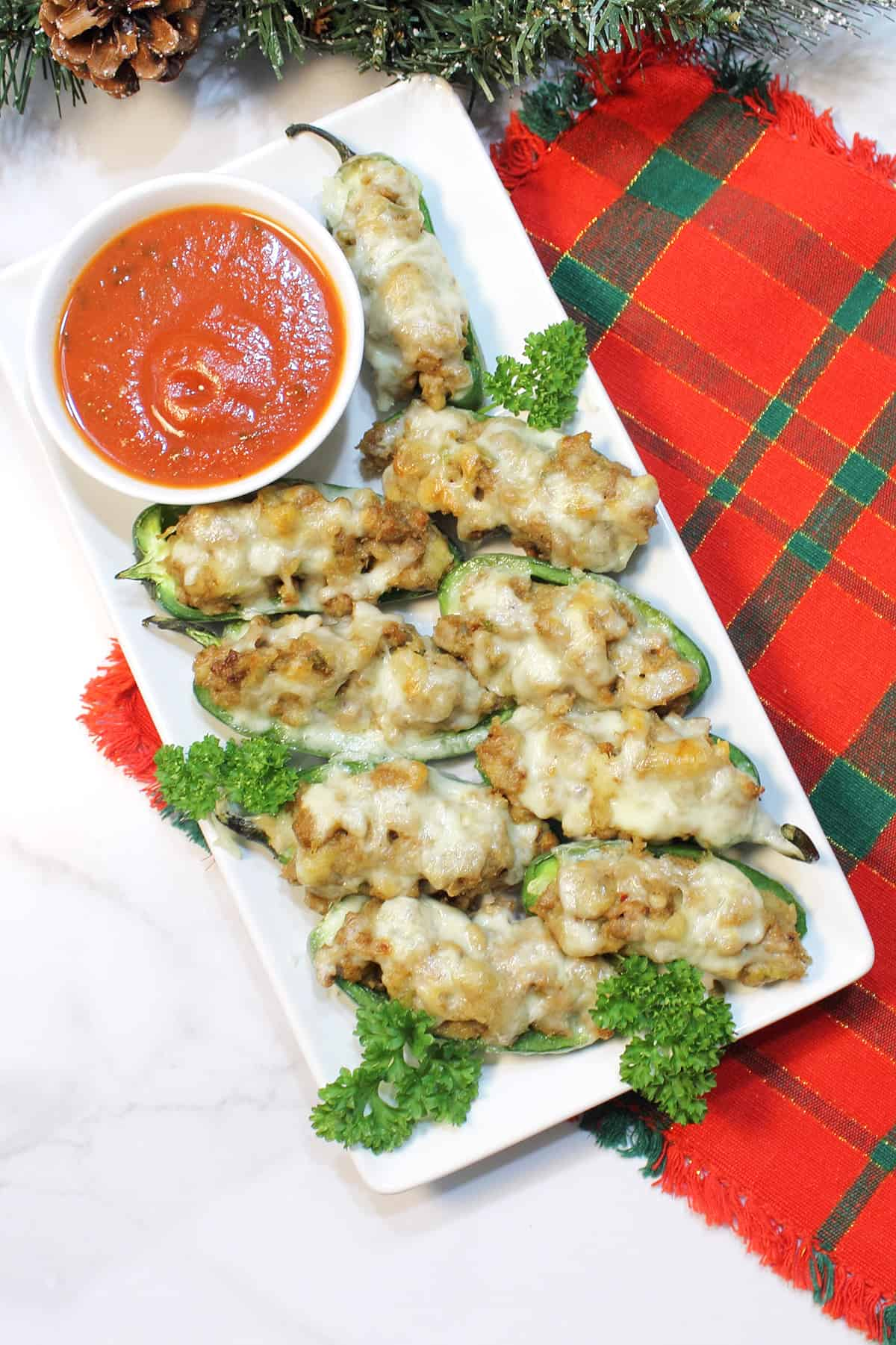 Overhead of stuffed jalapeno poppers with sausage on white serving plate with red plaid placemat.