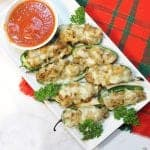 White platter with stuffed jalapenos with marinara on plaid placemat.