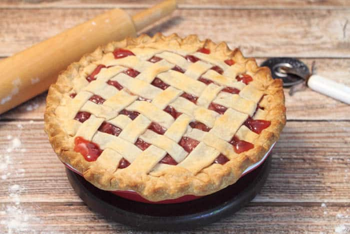 Baked Cherry Pie on wooden table with rolling pin.