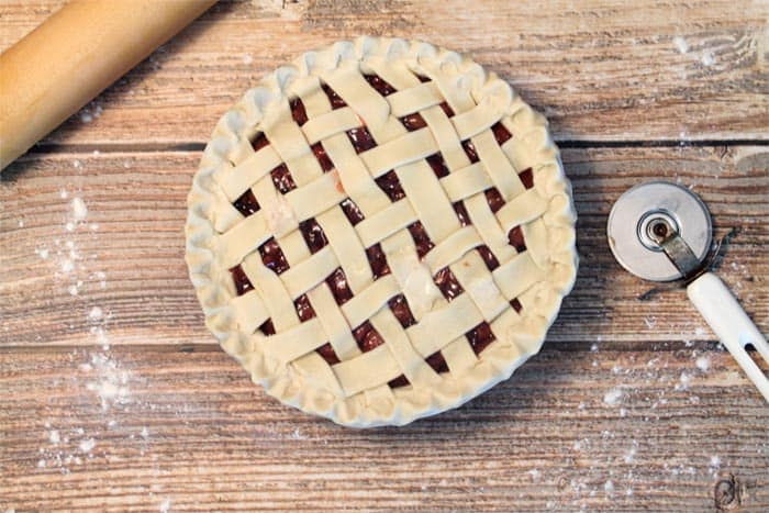 Cherry Pie with lattice crust on wooden table prior to baking.
