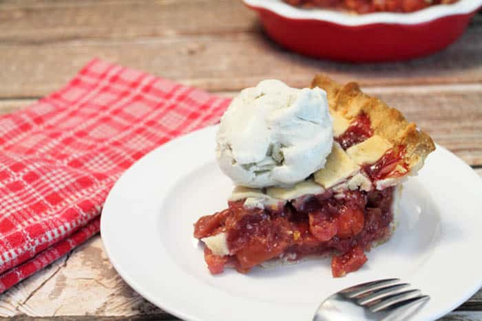 Slice of pie on white plate with ice cream on top.