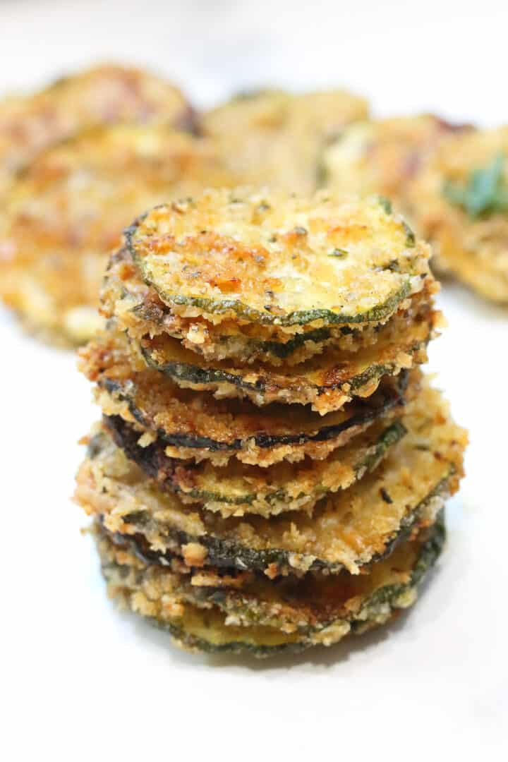 Stack of zucchini chips on white table.