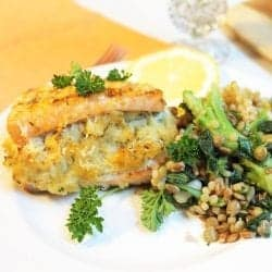 Closeup of crab stuffing in plated salmon with a side of vegetables and lemon slice.