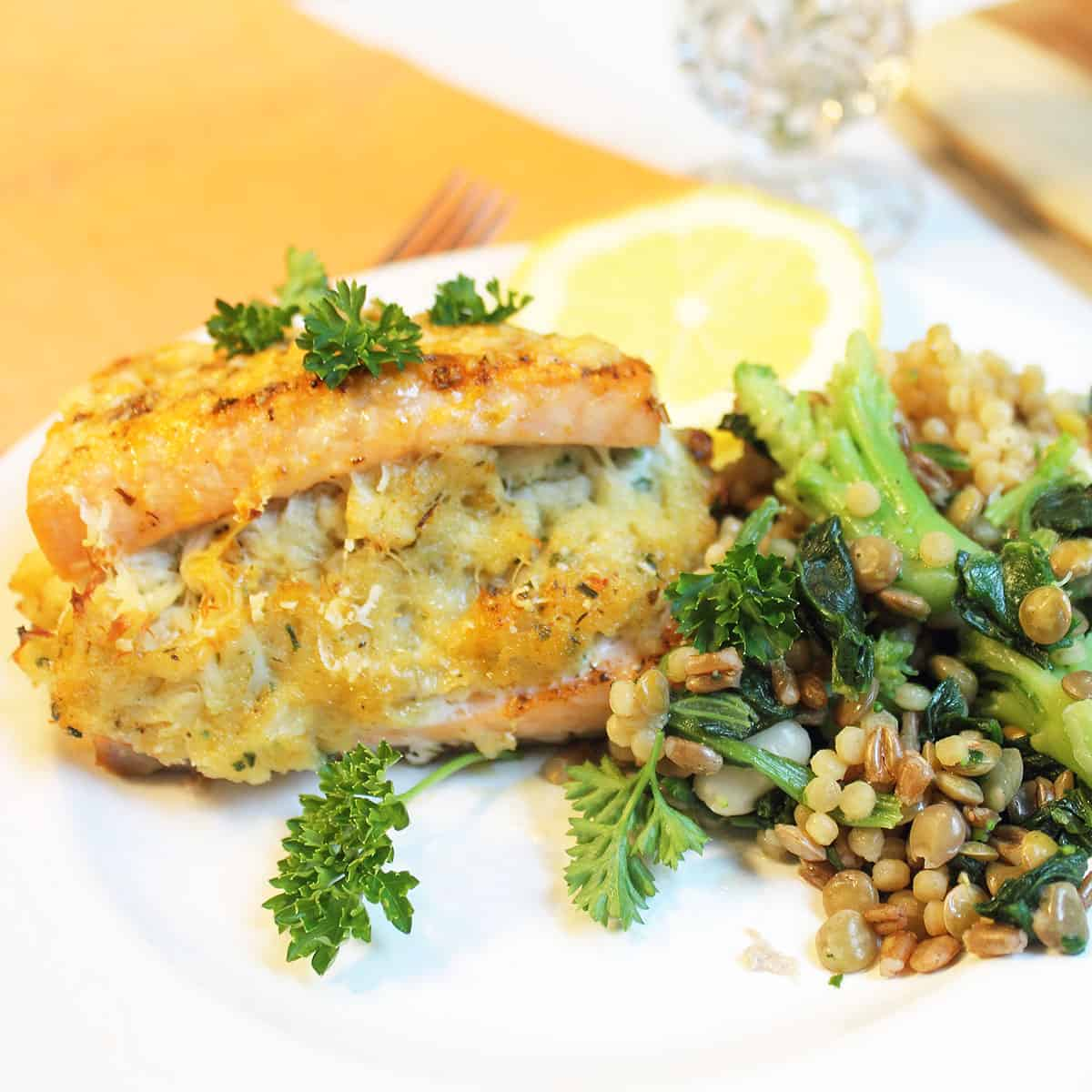 Closeup of crab stuffing in salmon on white plate.