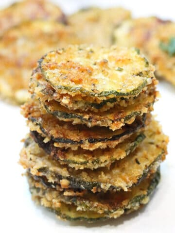 Stack of zucchini chips with more in back.