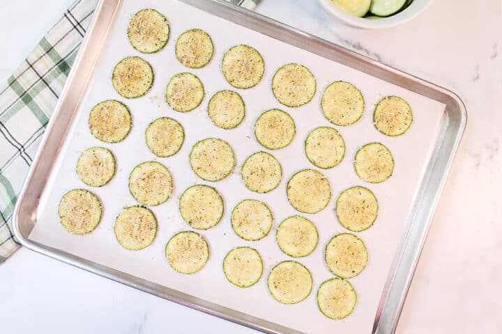 Zucchini slices on parchment lined cookie sheet ready to bake.