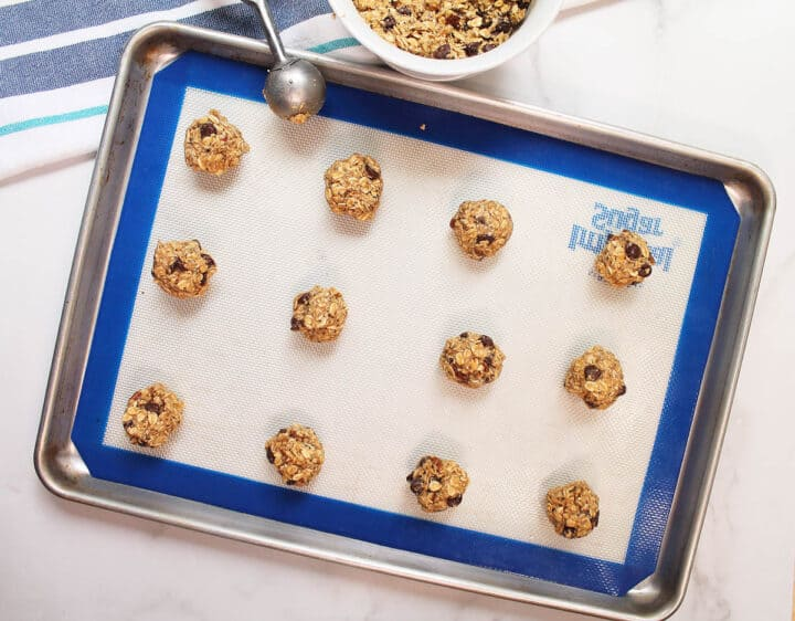 Scooped dough on lined cookie sheet.