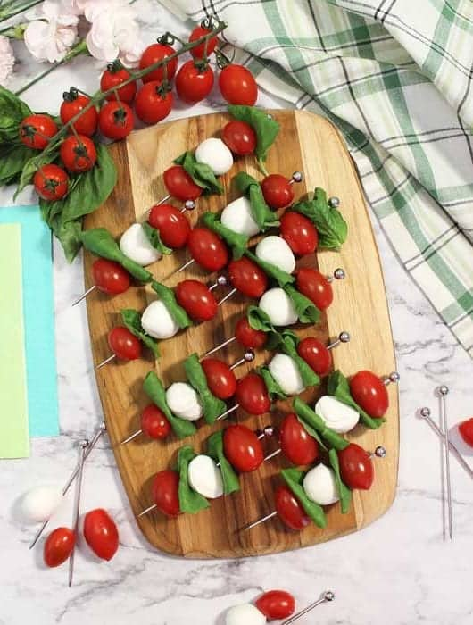 Tomato, basil and mozzarella threaded on skewers on wooden cutting board with tomatoes on vine in background