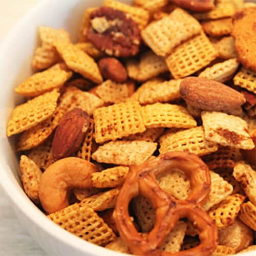 Closeup of GF Chex Mix in white bowl showing pretzels, chex square, pretzels and nuts.