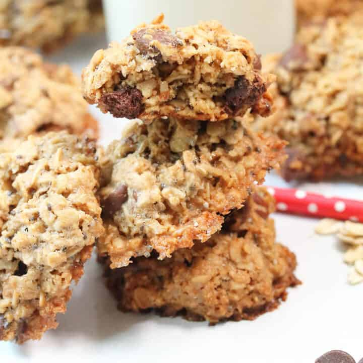 Stacked oatmeal chocolate chip cookies on white table.