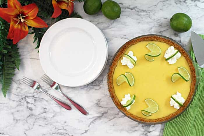 decorated whole key lime pie on marble background with plates beside it.