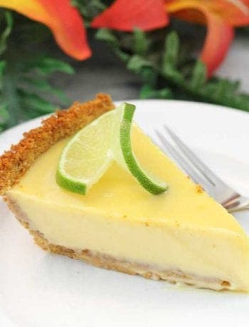 Slice of key lime pie with flowers in background.