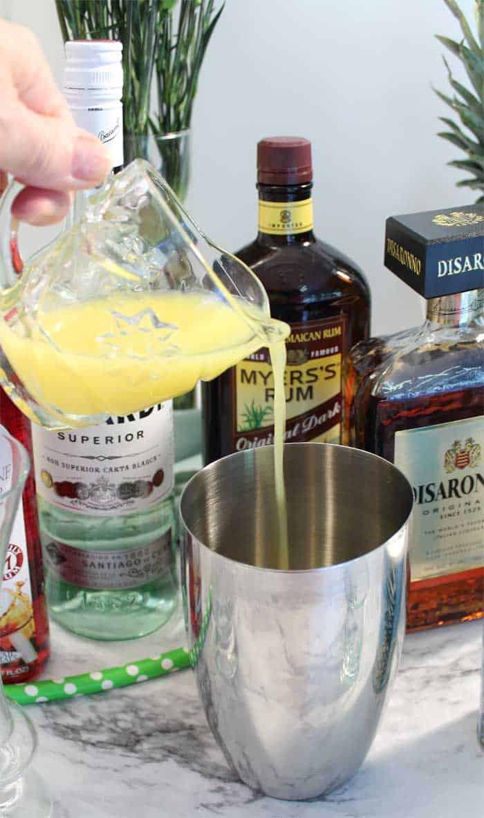 adding orange juice to shaker