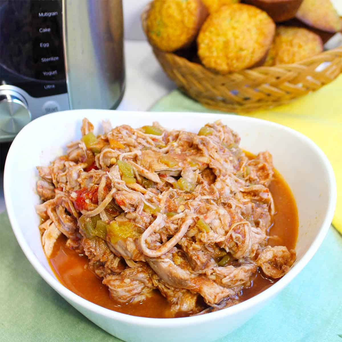 Cola Pulled Pork in bowl by Instant Pot and corn muffins.