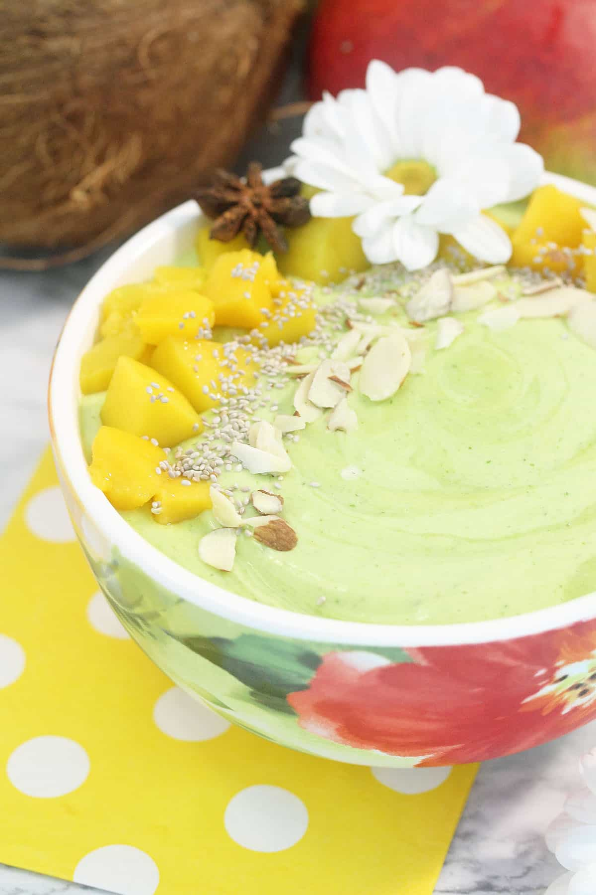Side view of closeup of finished smoothie in bowl with coconut and mango behind it.