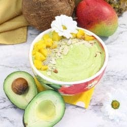 Mango green smoothie bowl with almonds mango and chia seed garnish and fruit all around.