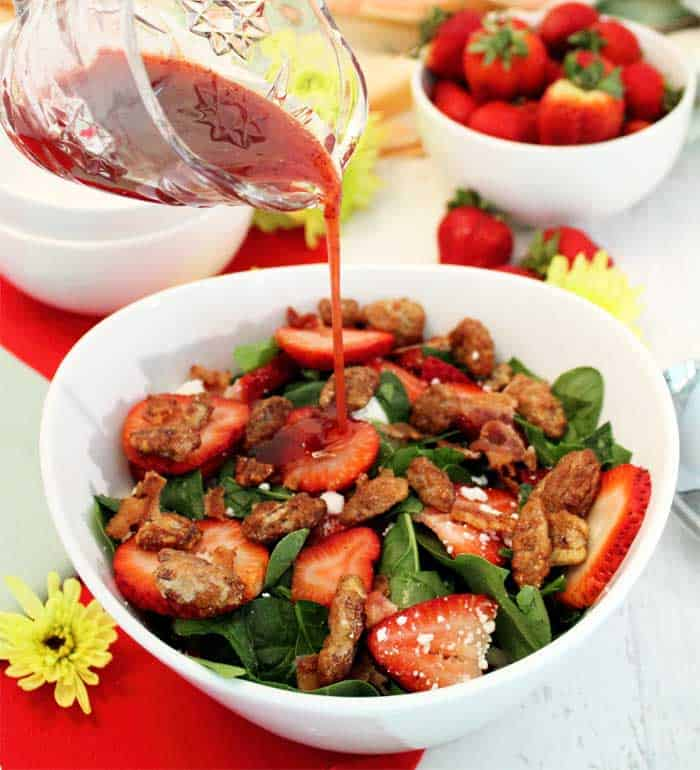 Drizzling vinaigrette on Spinach Strawberry Salad with Goat Cheese
