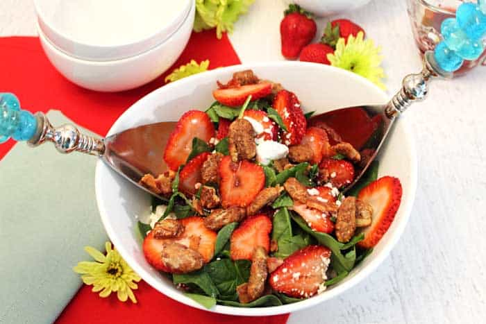 Tossing Spinach Strawberry Salad in white bowl