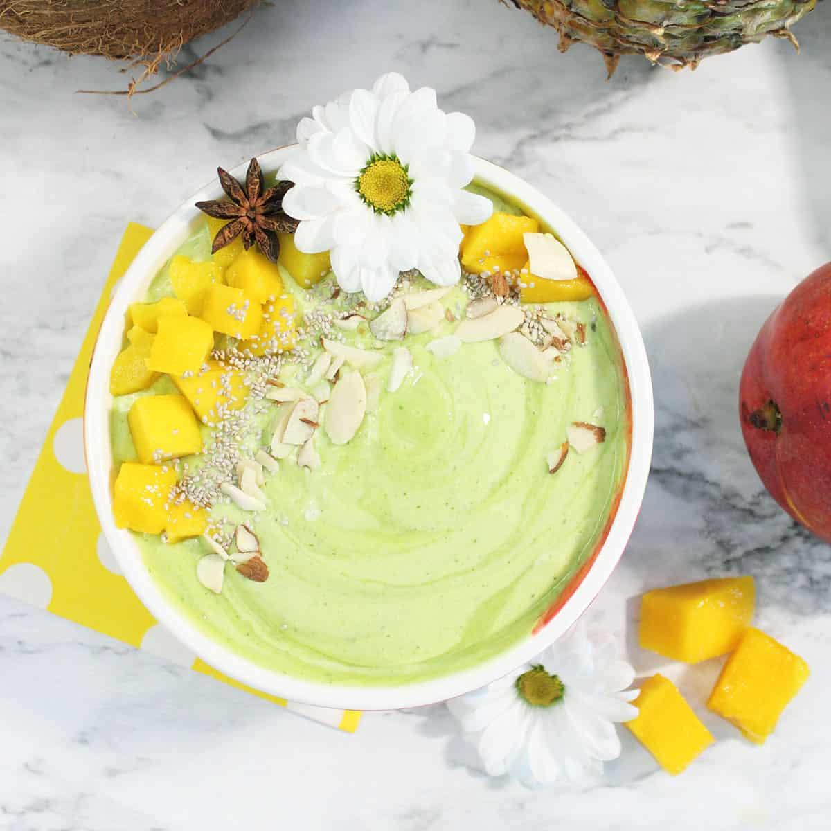 Green Pina Colada Smoothie in bowl on white table with mango pieces around bowl.