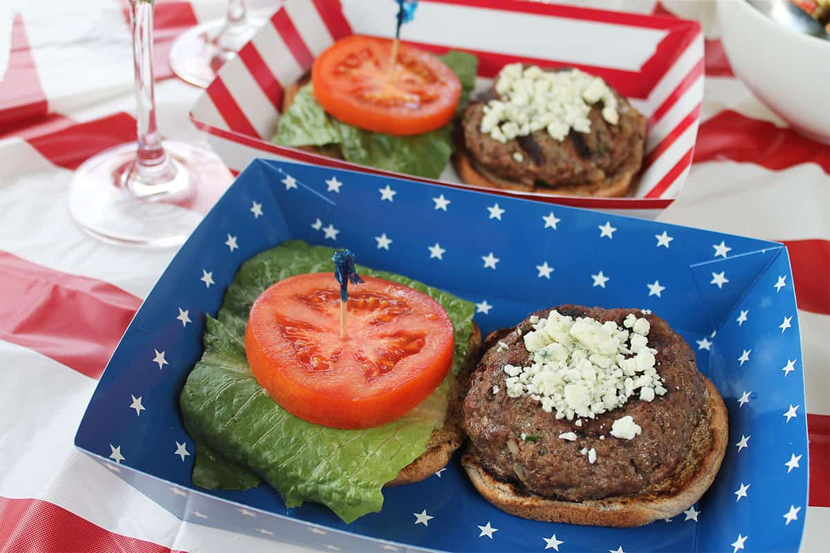 Bleu Cheese Hamburger on bun with lettuce and tomato in a red white and blue paper dish.