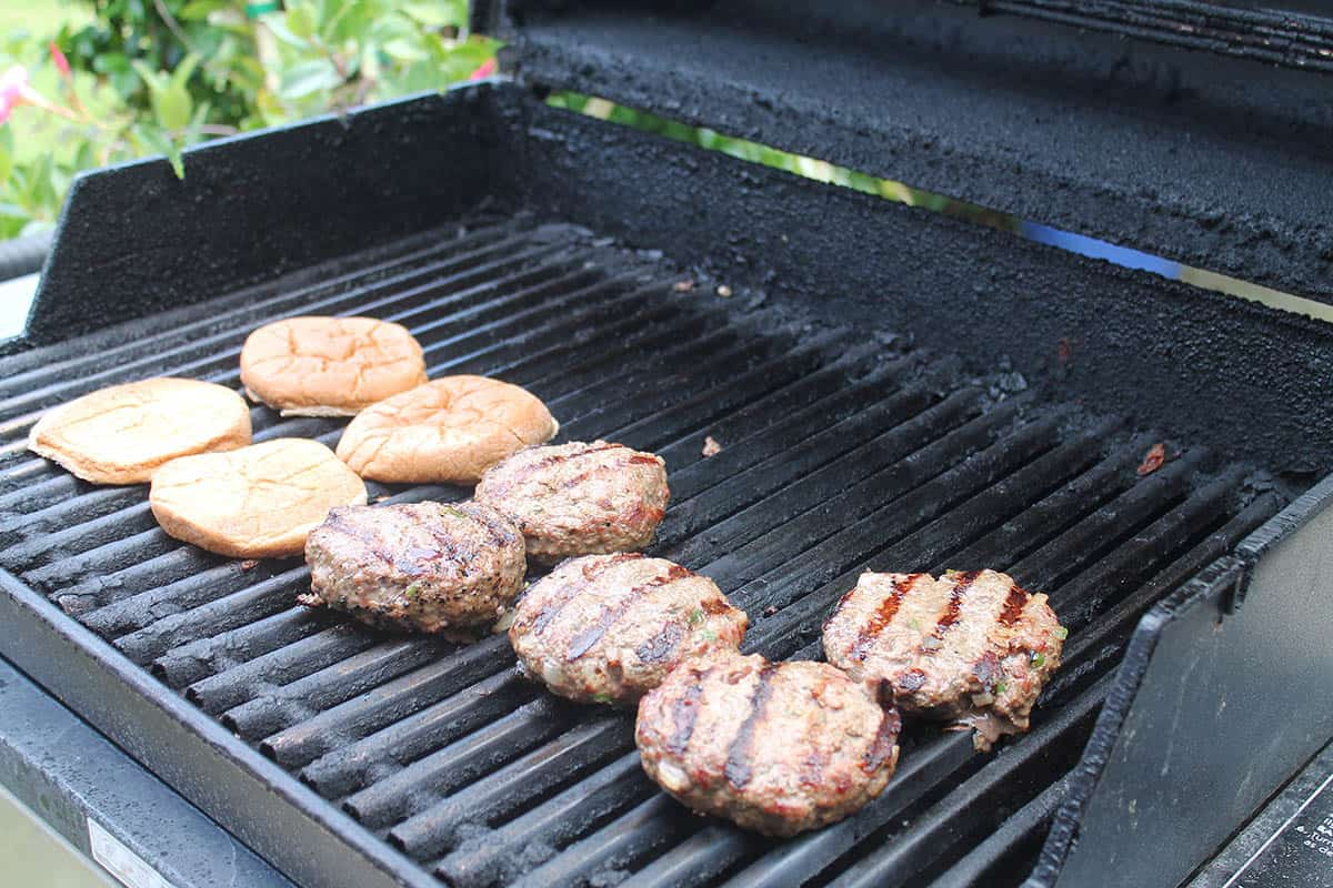 Grilling hamburgers and rolls on grill.