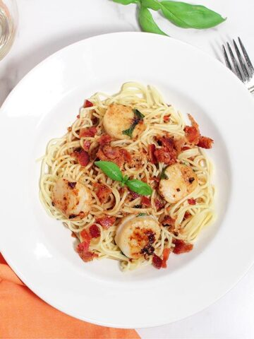 Overhead of serving of basil scallops over spaghetti in white bowl.