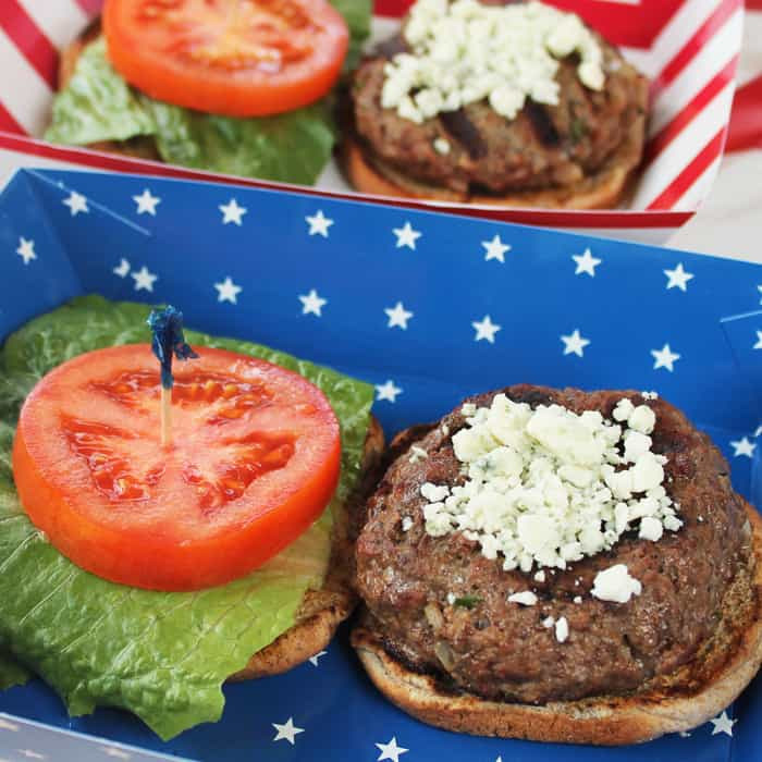 Grilled hamburger on bun with lettuce and tomato and topped with blue cheese set in a blue starred dish.