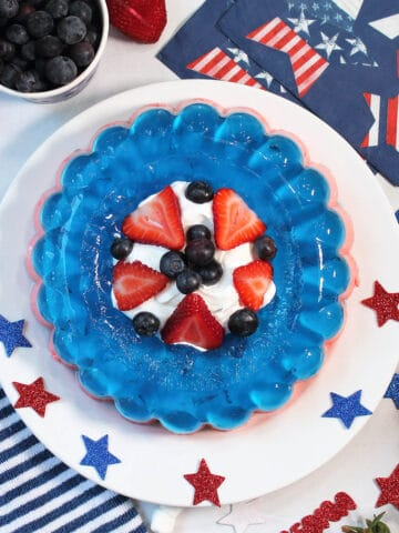 Overhead of red white and blue jello salad with patriotic napkins and blueberries.