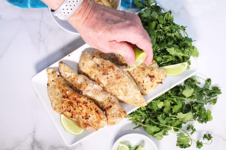Squeezing lime over cooked chicken on white platter.