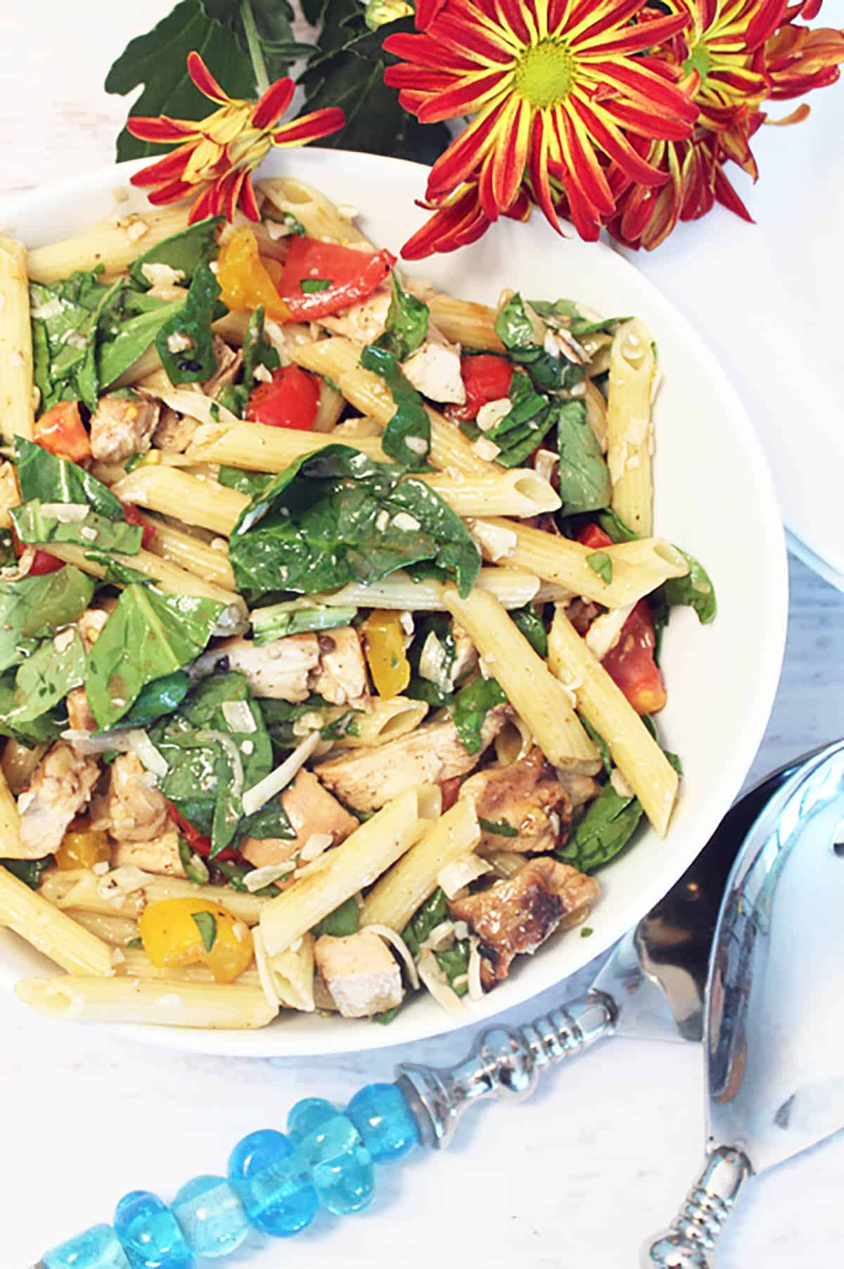 Chicken Pasta Salad in bowl with red flowers and blue handled servers.