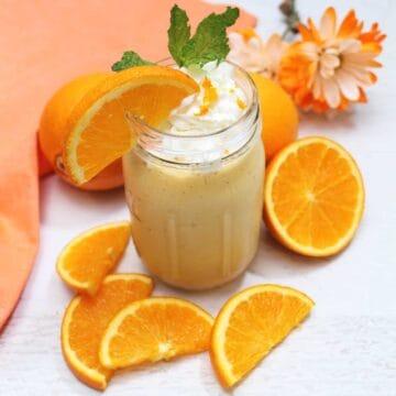 Banana Orange Smoothie with slice of orange and mint garnish and orange napkin with oranges around it.