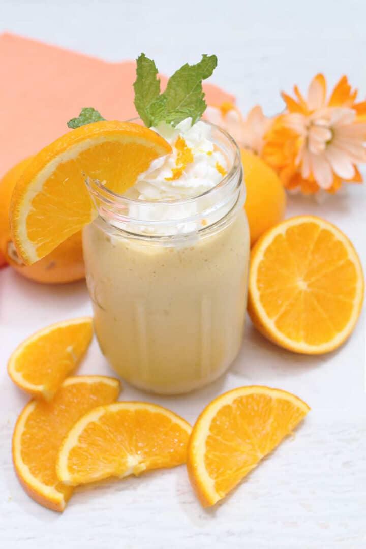Orange Creamsicle Smoothie on white table with orange slices around it.