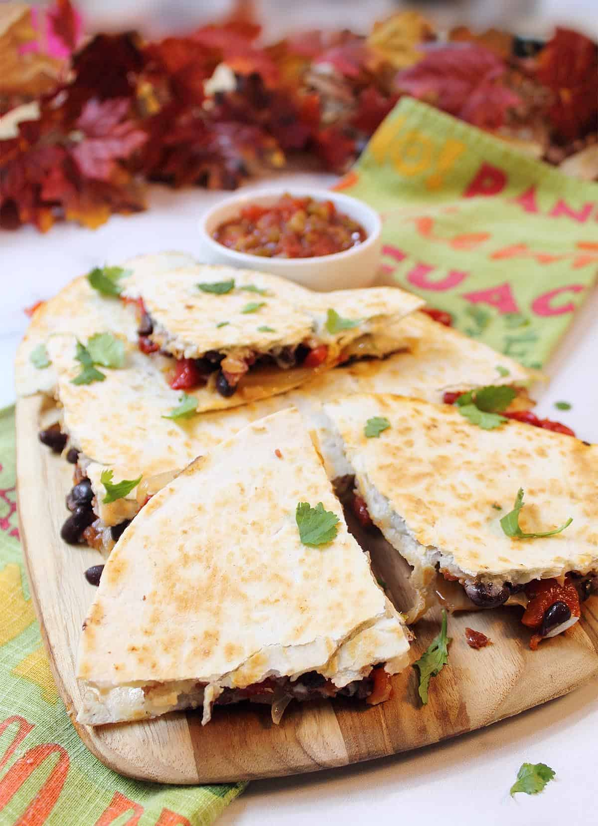 Cut roasted pepper quesadillas on board showing with salsa in back on top of Spanish worded towel.