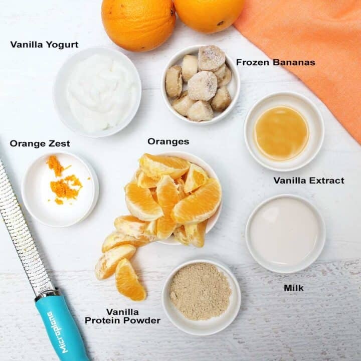 Ingredients on white table with zester and oranges.