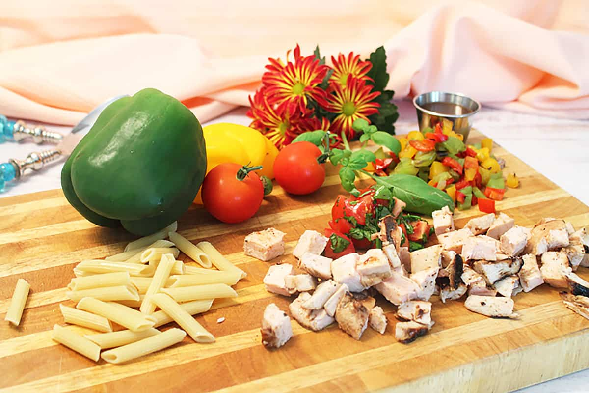 Chicken Pasta Salad ingredients on wooden cutting board.