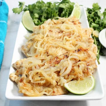 Chicken topped with onions on white platter with lime slices.