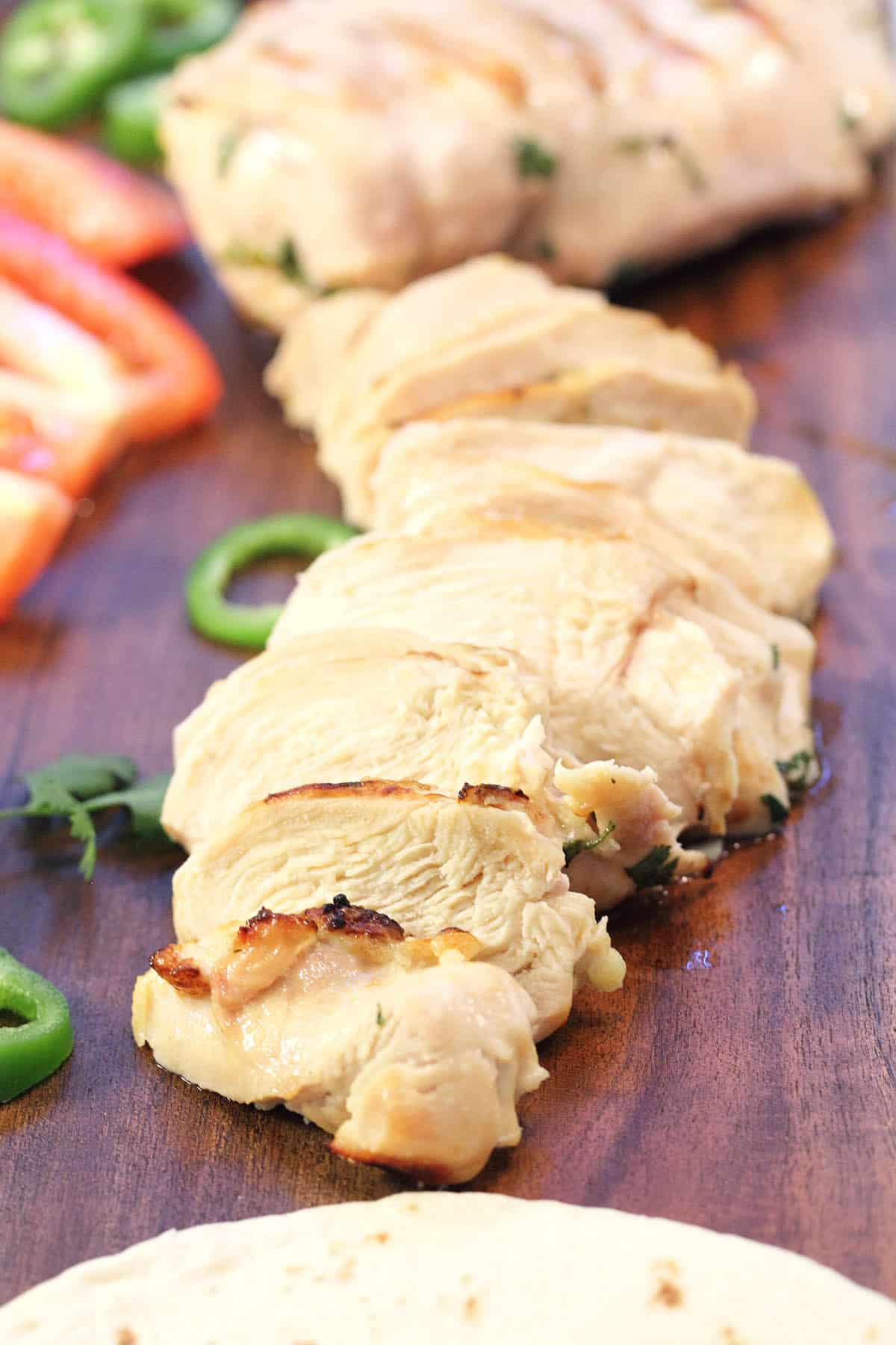 Closeup of moist sliced chicken on wooden board.