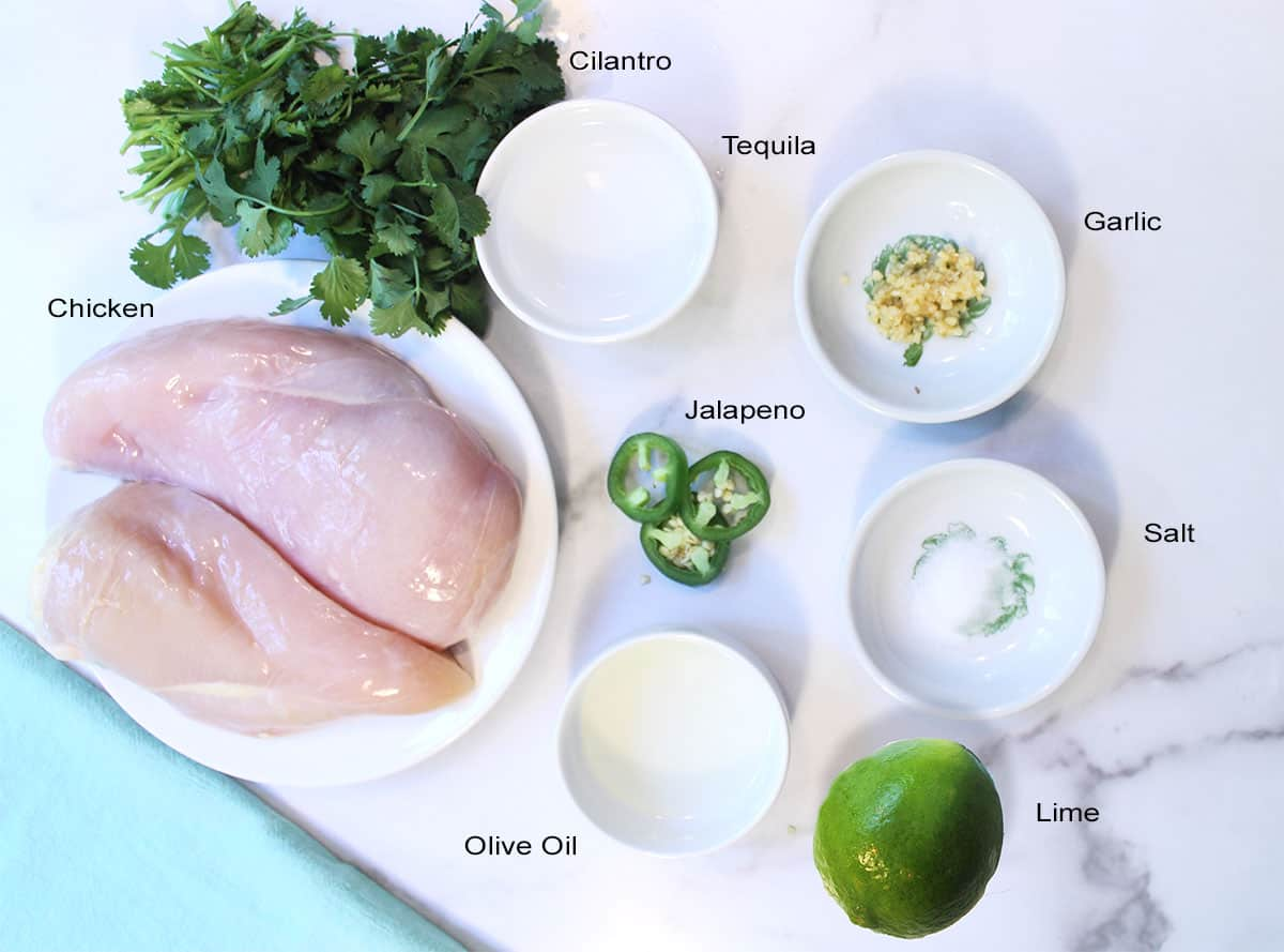Ingredients for tequila chicken laid out on white marble table.
