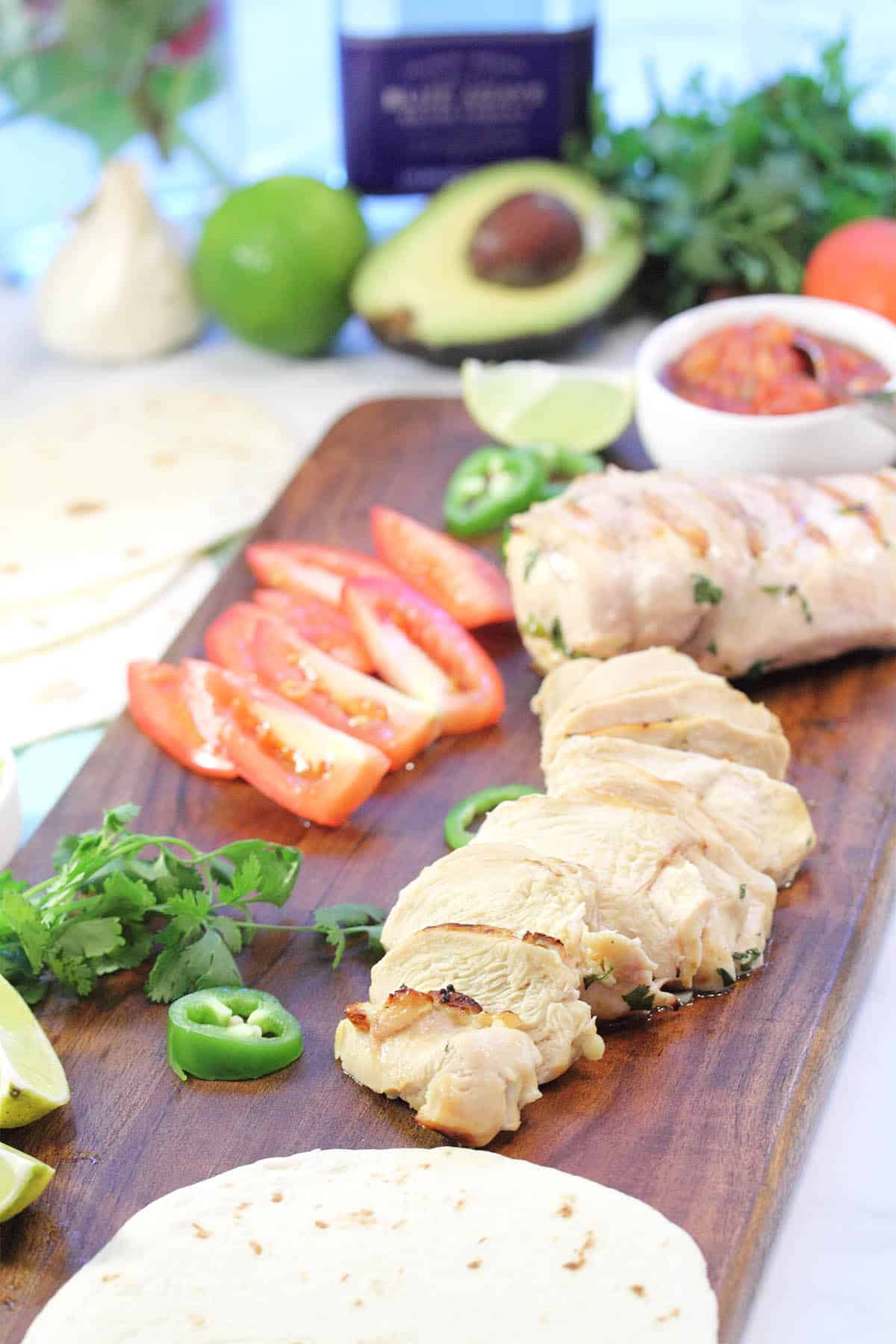 Sliced and whole grilled chicken on wooden board with sliced tomatoes jalapeno and salsa.