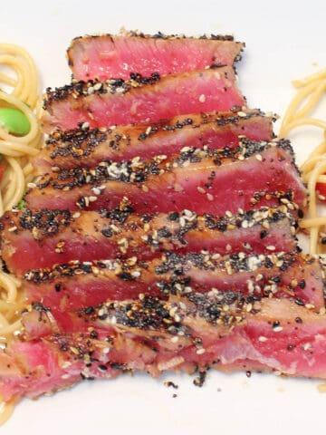 Closeup of sesame tuna dinner on white platter.
