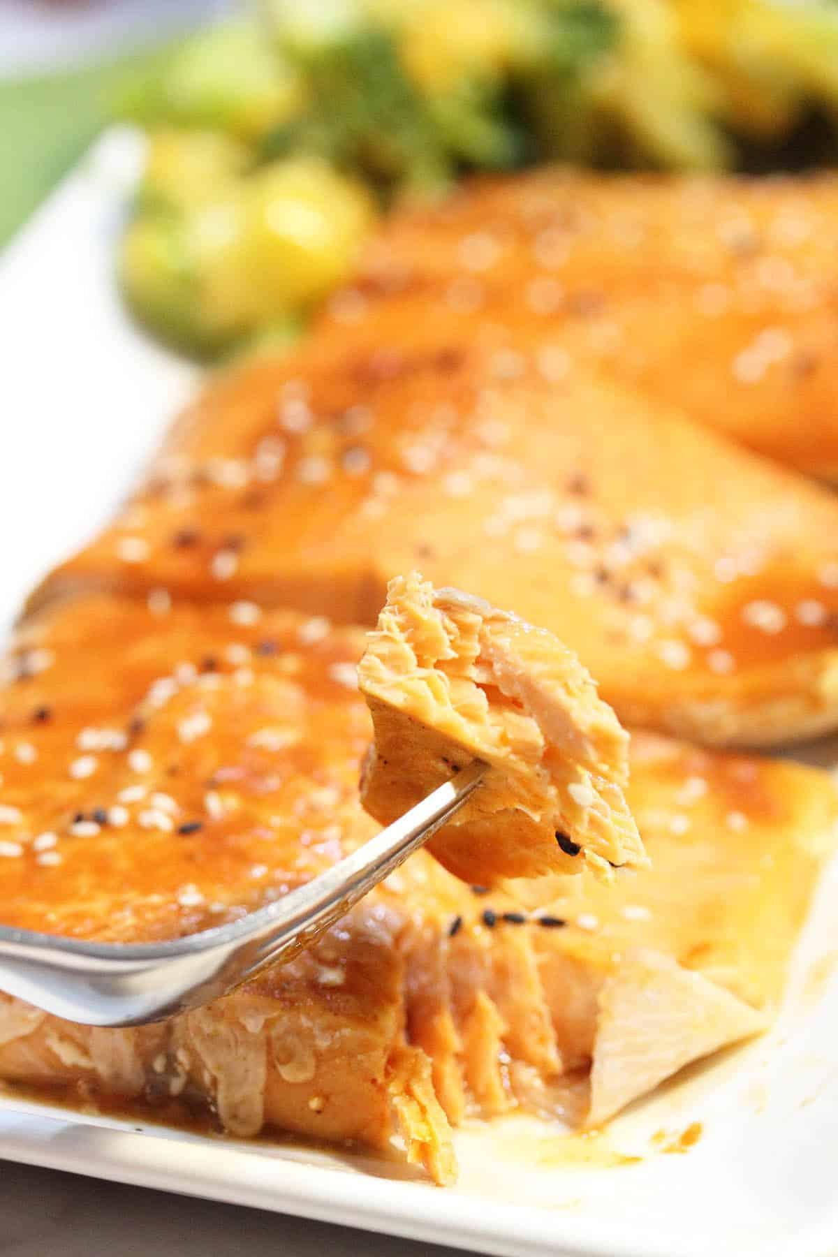 Bite of salmon on fork over white platter.