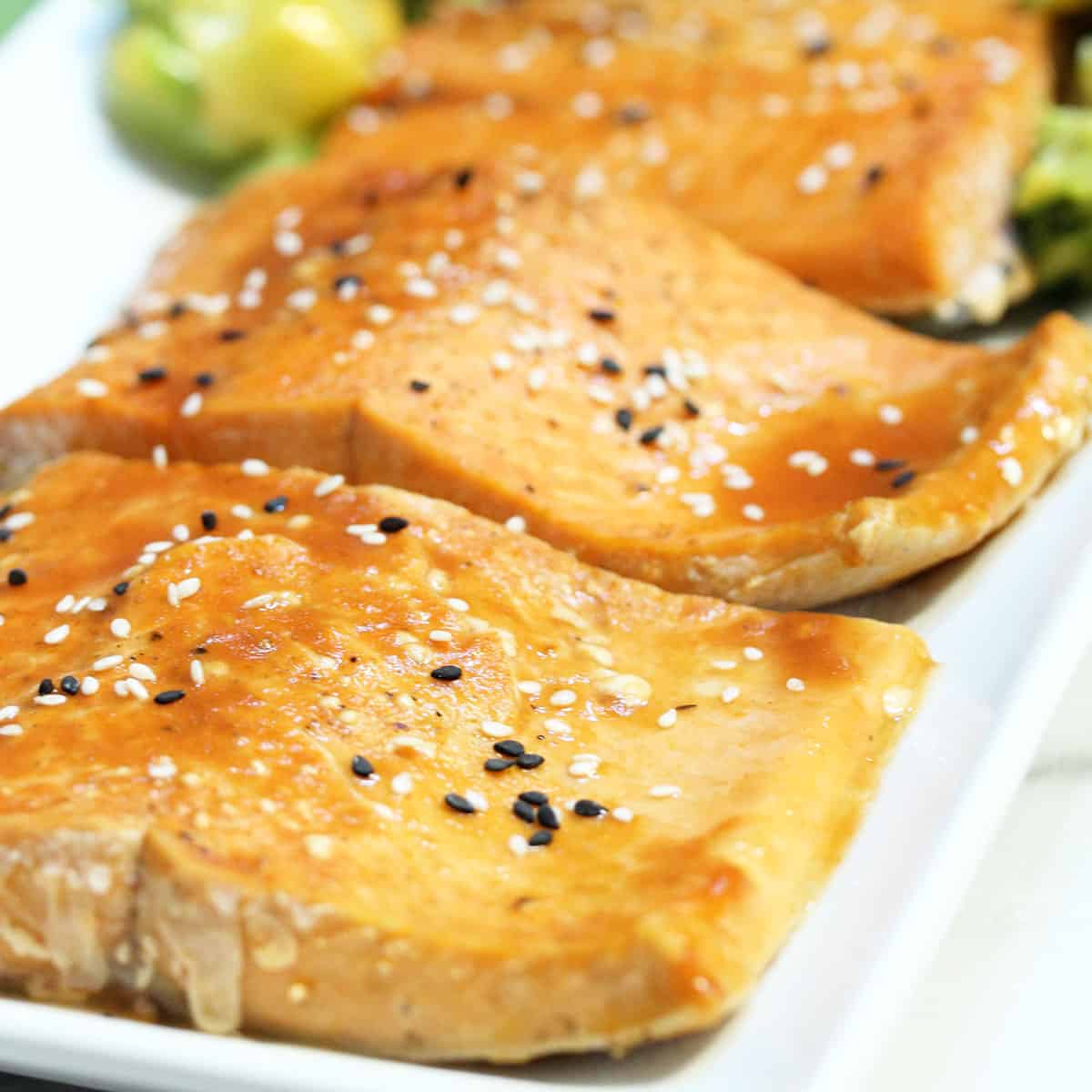 Closeup of broiled salmon on white platter.