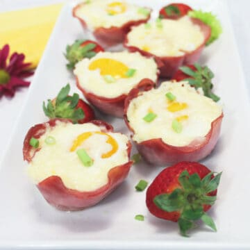 Platter of ham cheese and egg cups with strawberries.