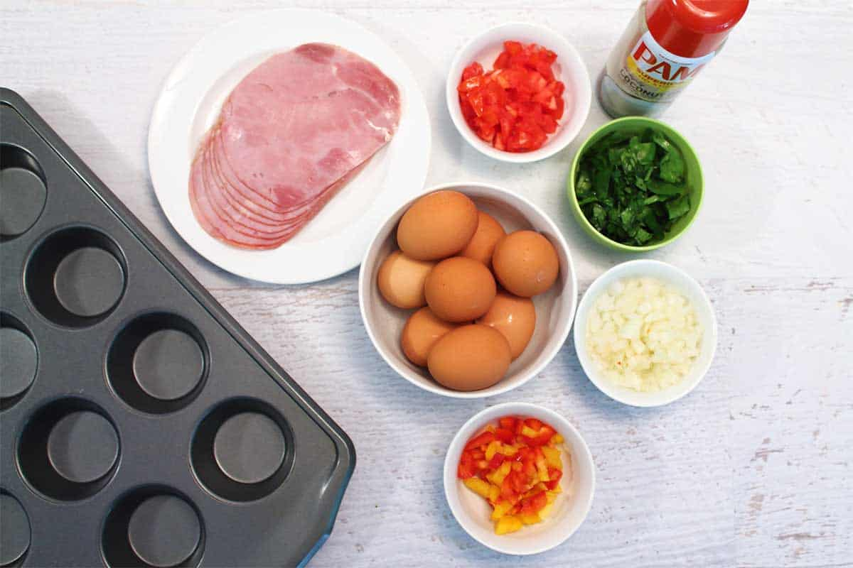 Ingredients for baked egg cups with muffin pan on white table.