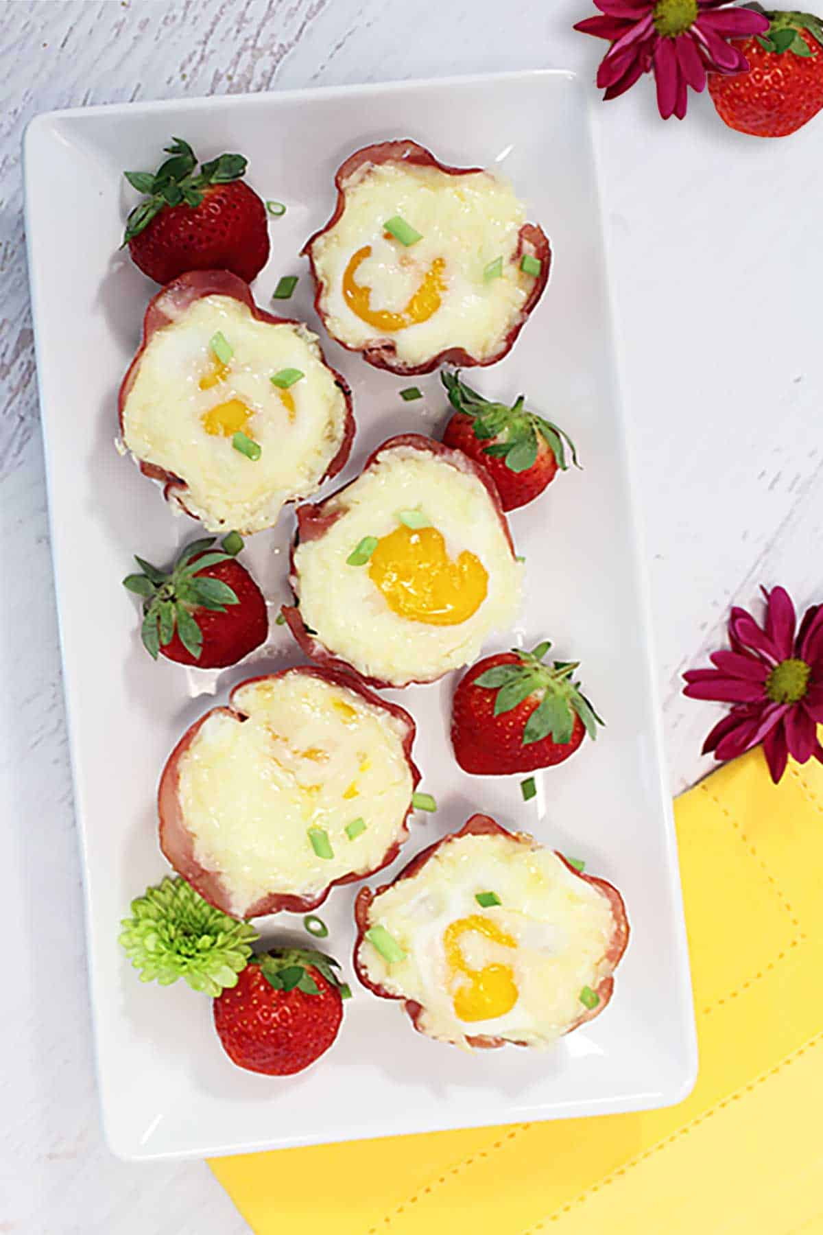 Overhead of ham cheese and egg cups on white platter with yellow napkin.