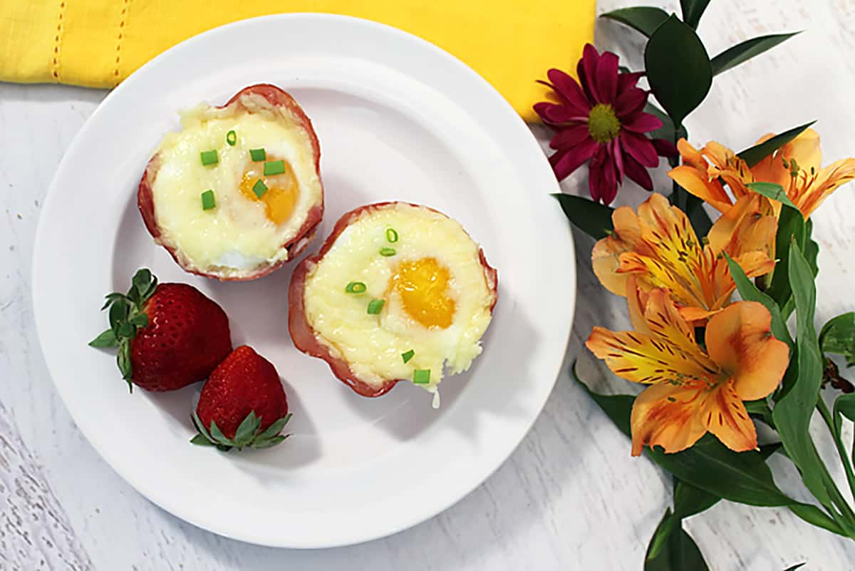 Overhead of two egg cups on white plate with flowers.