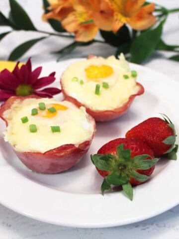A serving of two egg cups on white plate with strawberries.