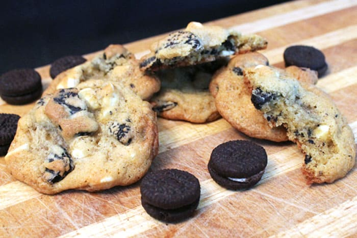 Cookies and Cream Cookies on cutting board with Oreos around them.