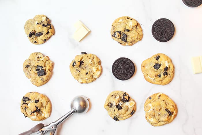 Cookies laid out with cookie scoop white chocolate and oreos on white marble.